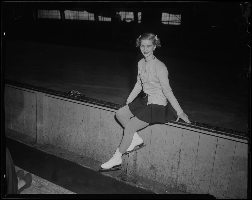Barbara Ann Scott sitting on the rink boards, with skates on