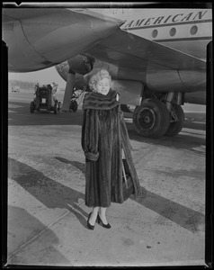 Zsa Zsa Gabor posing in front of airplane