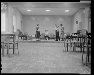 Group of three students and an instructor on a stage with tables and chairs in the foreground