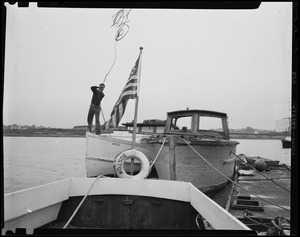 Man on boat number 4D331, throwing a rope in preparation for Hurricane Edna