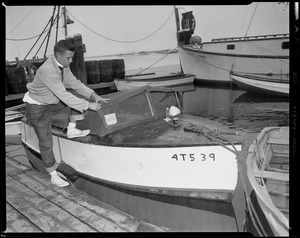 Man pulling tarp onto boat number 4T539 in preparation for Hurricane Edna