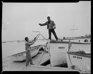 Man on boat number 4N814, throwing rope to another man on the dock, preparing for Hurricane Edna