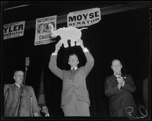 Leverett Saltonstall holding a Republican party elephant placard in above his head
