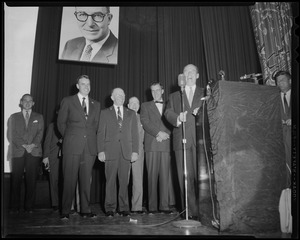 Adlai Stevenson standing at podium on stage with several others behind him