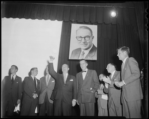 Adlai Stevenson on stage waving and addressing crowd with several others including his sons (far left) and John F. Kennedy (far right)