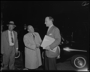 Adlai Stevenson shaking hands with his son Adlai Stevenson III outside next to a car