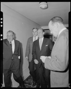 Adlai Stevenson and his son Adlai Stevenson III walking down a hall with 2 other men