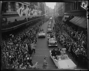 Adlai Stevenson in first car of campaign motorcade with crowds on either side