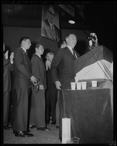Adlai Stevenson at podium, with his sons behind him