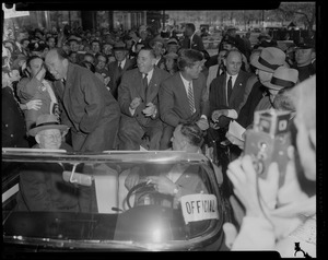 Adlai Stevenson in convertible with Foster Furcolo and John F. Kennedy, surrounded by a crowd