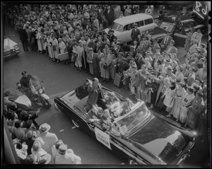 Adlai Stevenson in convertible with Foster Furcolo, John F. Kennedy and two others, surrounded by a crowd