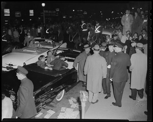 Adlai Stevenson exiting a convertible as mounted police watch