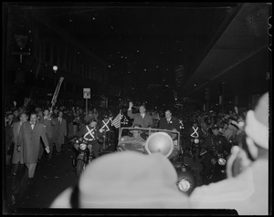Adlai Stevenson and Paul Dever waving from car driving down parade route at night