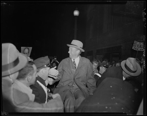 Adlai Stevenson seen in crowd shaking hands with those around him