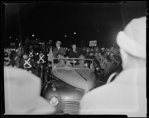 Adlai Stevenson and Paul Dever in car moving through parade with police escort