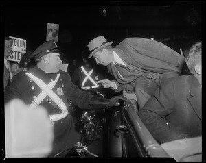 Adlai Stevenson talking to a police officer from a convertible