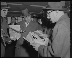 Adlai Stevenson looking at newspapers with group