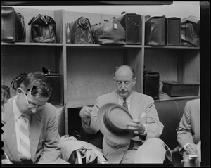 Adlai Stevenson sitting in luggage area and removing hat