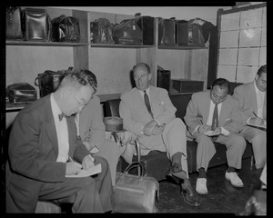Adlai Stevenson, seated with others in a luggage area
