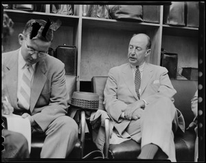 Adlai Stevenson seated and talking to another man in a luggage area