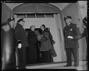 Adlai Stevenson speaking with a man in an academic robe in a doorway