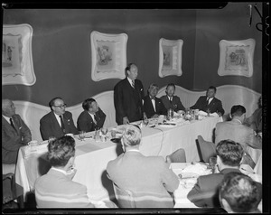 Adlai Stevenson addressing a group of people at a dinner table