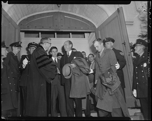 Adlai Stevenson shaking hands with a man in academic robe in a doorway