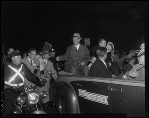 Adlai Stevenson sitting on the back of a car with a police officer beside them