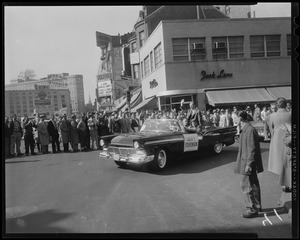 Adlai Stevenson sitting in a car with a crowd of people in the background