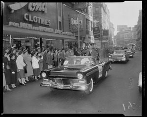 Adlai Stevenson standing and waving from a car during a rally