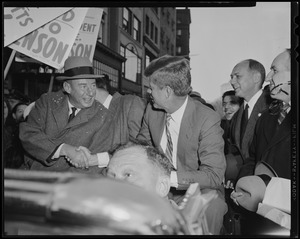 Adlai Stevenson and John F. Kennedy shaking hands in car during parade