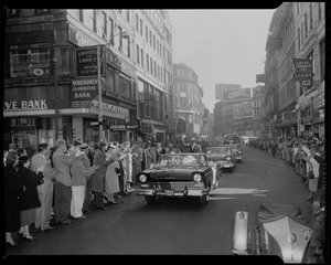 Adlai Stevenson waving from front car in a parade