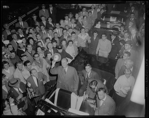 View of Adlai Stevenson standing in a car and the people surrounding him from above