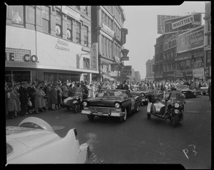 Adlai Stevenson in car in a parade with crowds on either side