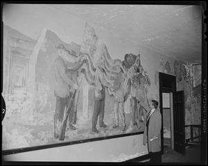Man looking at a mural on a wall depicting soldiers and the American flag