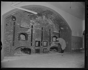 Man looking at ovens in wall at Fort Warren