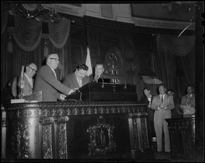 Filmstage-television comedian Jackie Gleason stands with other men at a speaker's podium as he addressed the House of Representatives at the State House