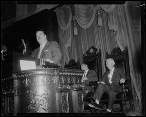 Filmstage-television comedian Jackie Gleason stands at a speaker's podium as he addressed the House of Representatives at the State House