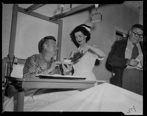 Arthur Godfrey smiling at nurse as she pours from the tea pot