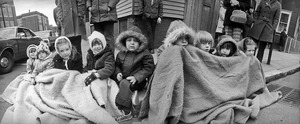 Kids keep warm under a curbside blanket at St. Patrick's Day Parade, Boston