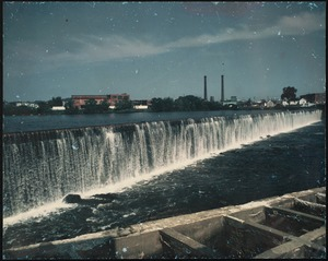 Water flowing over a dam with cityscape