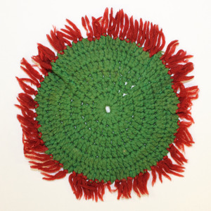 Green doily or caster with red fringe, made by Laura Bridgman
