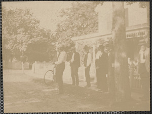Six unidentified men standing by street with one holding bicycle