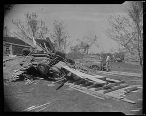 Two men standing near overturned car and other debris from tornado