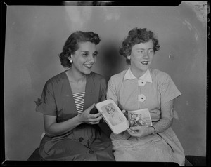 Two women posing with photographs