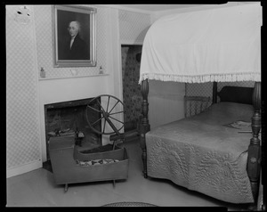 Bedroom with painting above fireplace, bed, crib, and spinning wheel, most likely at Adams National Historical Site