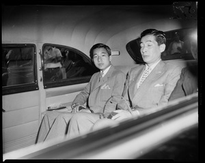Crown Prince Akihito seated in the backseat of a vehicle with another man
