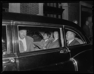 Crown Prince Akihito seated with three other men in the backseat of a vehicle