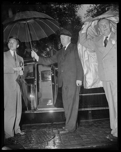 Crown Prince Akihito standing next to open door of vehicle with man holding umbrella open and other man covering head with coat