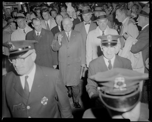 Edward McCormack, Harry Truman, John F. Kennedy, and large crowd walking, with police officers leading
